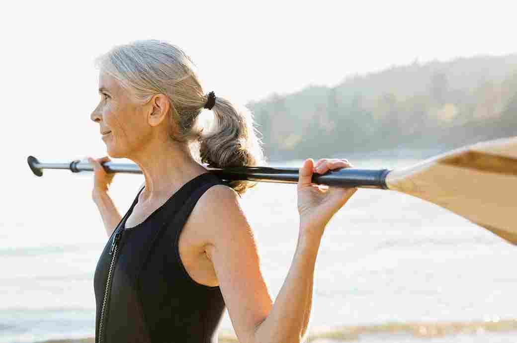 Yaşlı bir kadın omuzunda kürek tutuyor